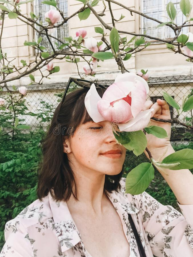 Stilfull bohoflicka som gör selfie med härliga rosa magnoliablommor på filial Hipsterflicka som luktar och poserar med magnolian royaltyfri bild