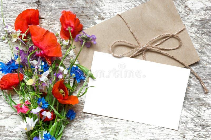 Stilfull brännmärka modell som visar dina konstverk tomt hälsningkort eller bröllopinbjudan med sommarvildblommor royaltyfria bilder