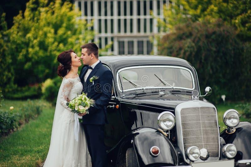 Stilfull brud och brudgum som poserar sensually nära den retro bilen med boh arkivbilder