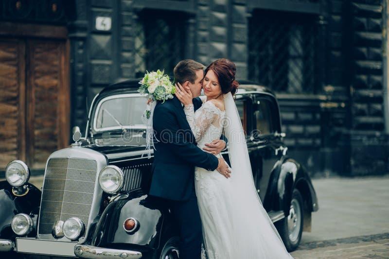 Stilfull brud och brudgum som poserar sensually nära den retro bilen med boh royaltyfri foto