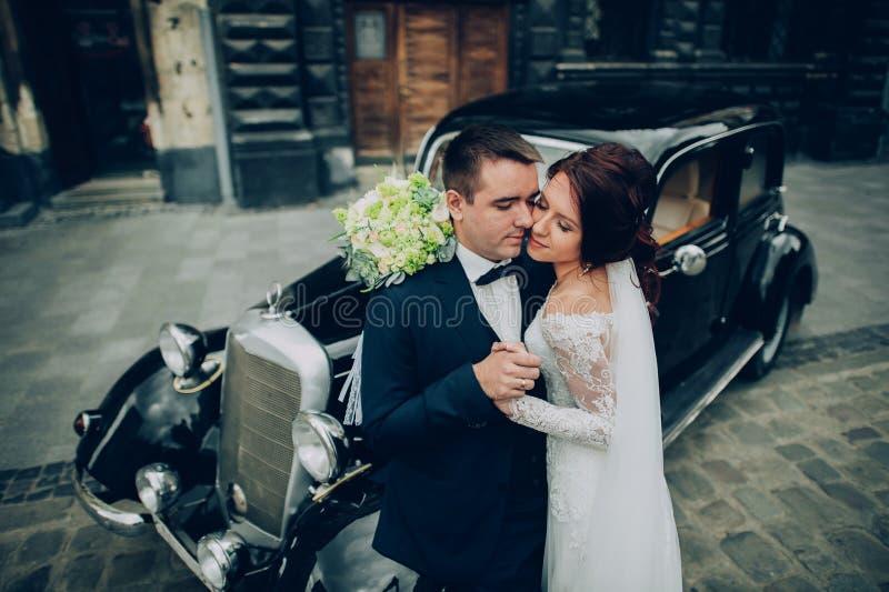 Stilfull brud och brudgum som poserar sensually nära den retro bilen med boh royaltyfria foton