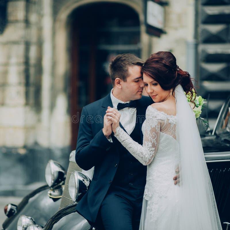 Stilfull brud och brudgum som poserar sensually nära den retro bilen med boh royaltyfria bilder