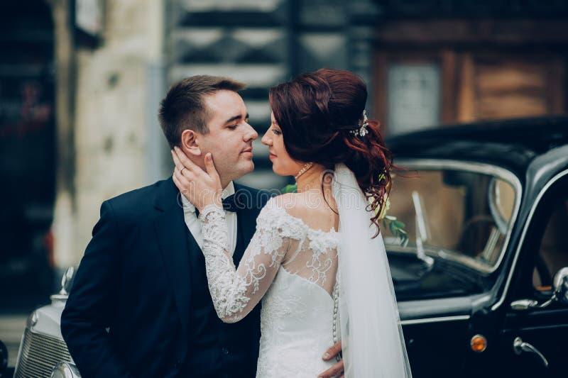 Stilfull brud och brudgum som poserar sensually nära den retro bilen med boh arkivfoto