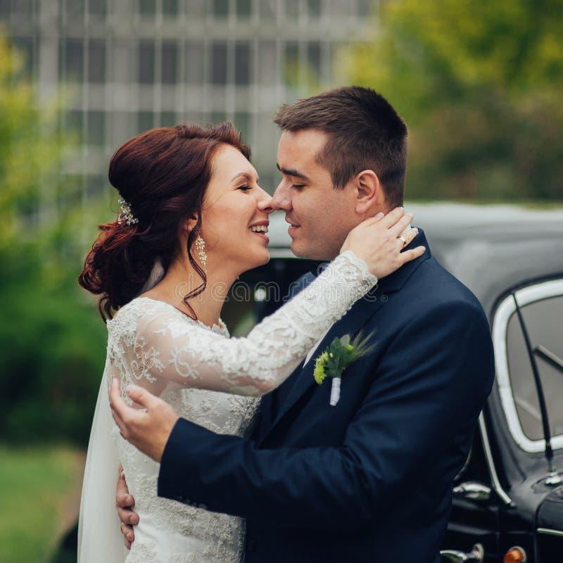 Stilfull brud och brudgum som poserar sensually nära den retro bilen med boh royaltyfri fotografi