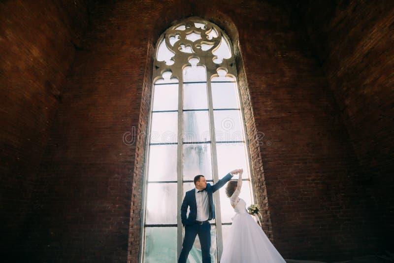 Stilfull brud och stilig elegant brudgumdans på bakgrunden av den lyxiga inre med det stora fönstret royaltyfri fotografi