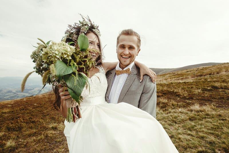 Stilfull brudgum som bär den lyckliga bruden och skrattar, boho som gifta sig Co royaltyfri foto