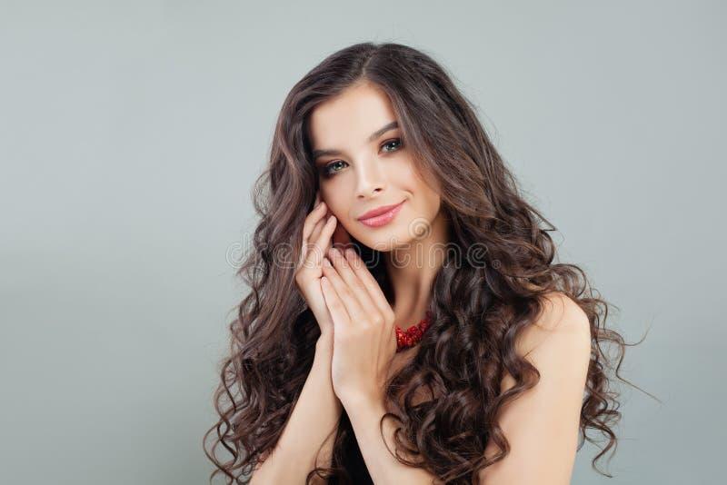 Stilfull brunettkvinna med den skinande lockiga frisyrståenden fotografering för bildbyråer