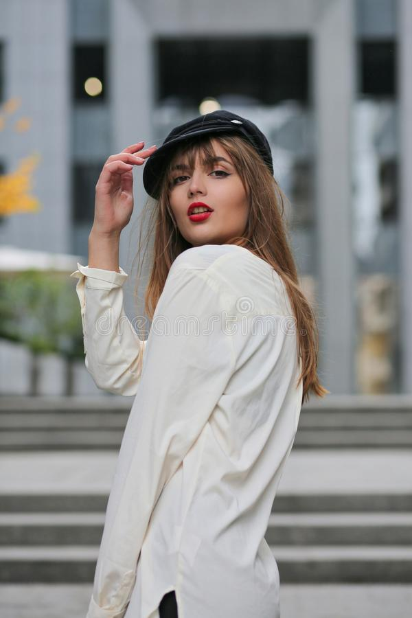 Stilfull brunettmodell som bär det stilfulla locket och vitskjortan, posi royaltyfri fotografi