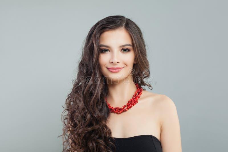 Stilfull brunettmodellkvinna med långt hår och halsbandet för röd korall, stående arkivfoton