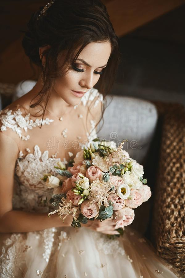 Stilfull bukett av rosa och vita blommor i händerna av den härliga modellflickan i moderiktig bröllopsklänning arkivbild