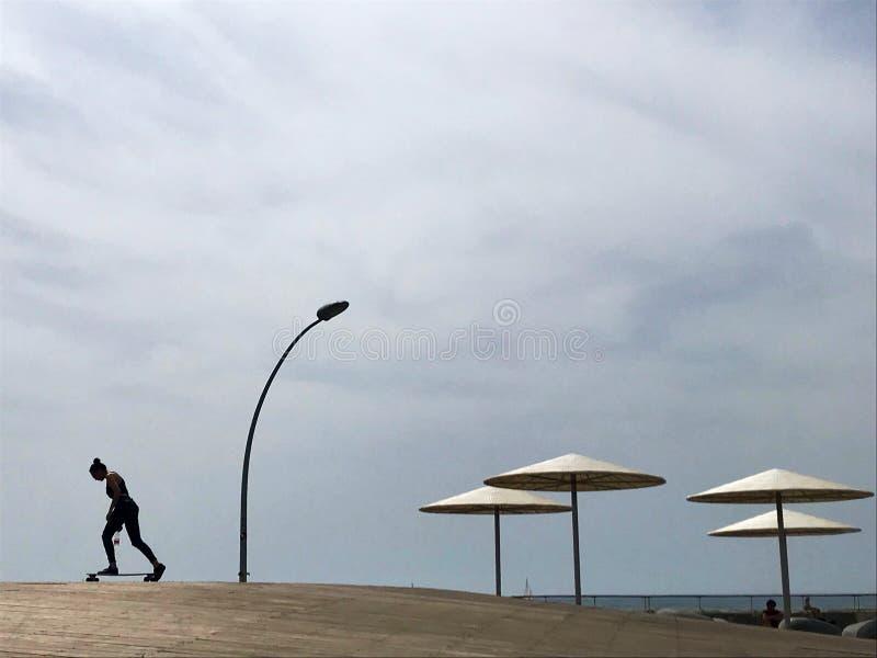 Stilfull dagdrivare i gul sand till solen sunbed på stranden arkivbilder