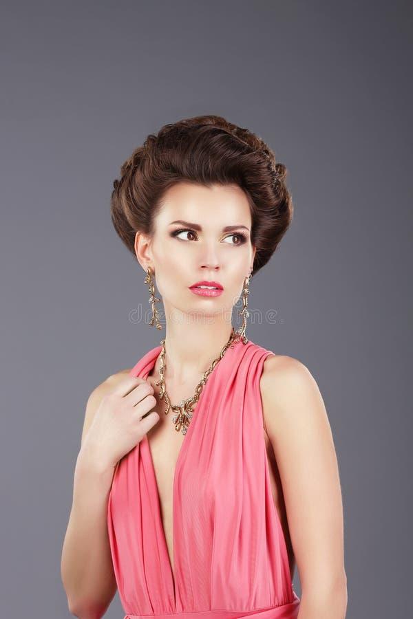 Stilfull dam i rosa färgklänning med dekorering fotografering för bildbyråer