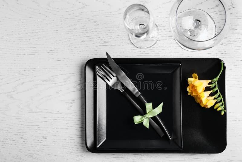 Stilfull elegant tabellinställning med freesia på vit träbakgrund, bästa sikt fotografering för bildbyråer