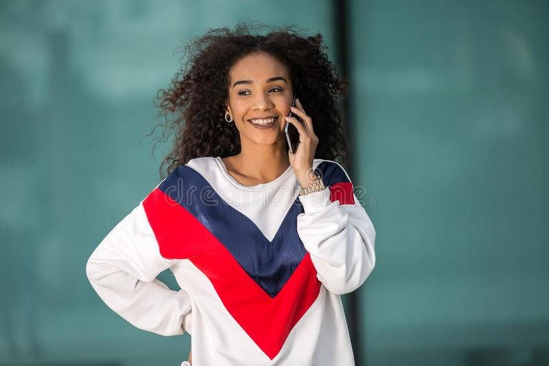 Stilfull etnisk kvinna som talar på telefonen arkivbilder