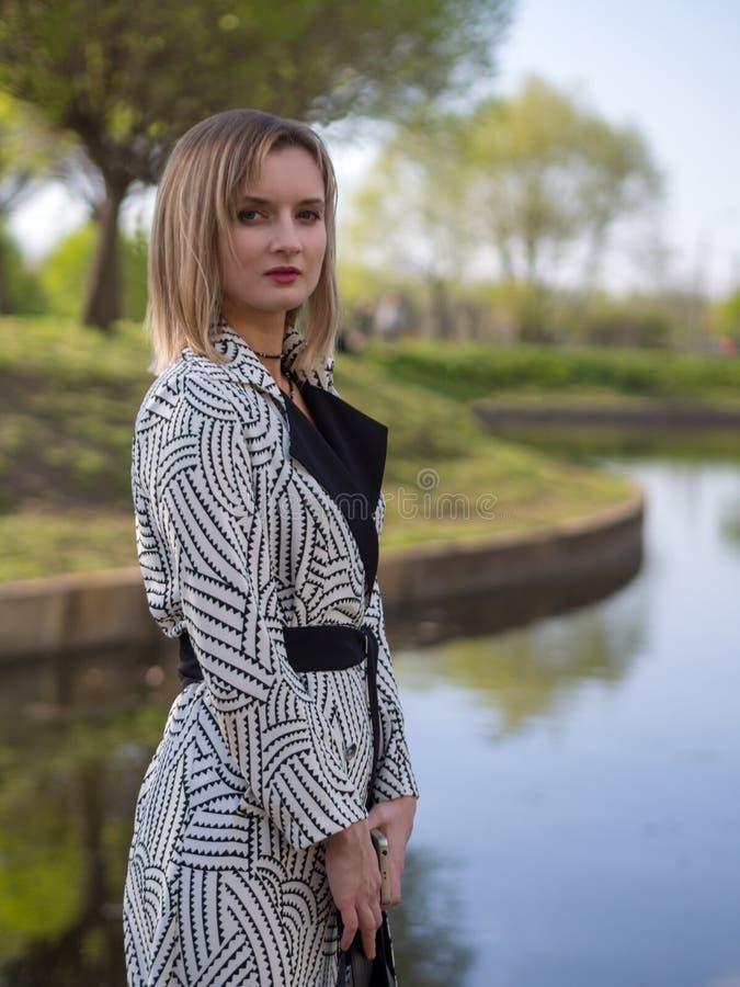 Stilfull europeisk ung kvinna i en regnrock, strumpbyxor, skor med häl royaltyfri fotografi