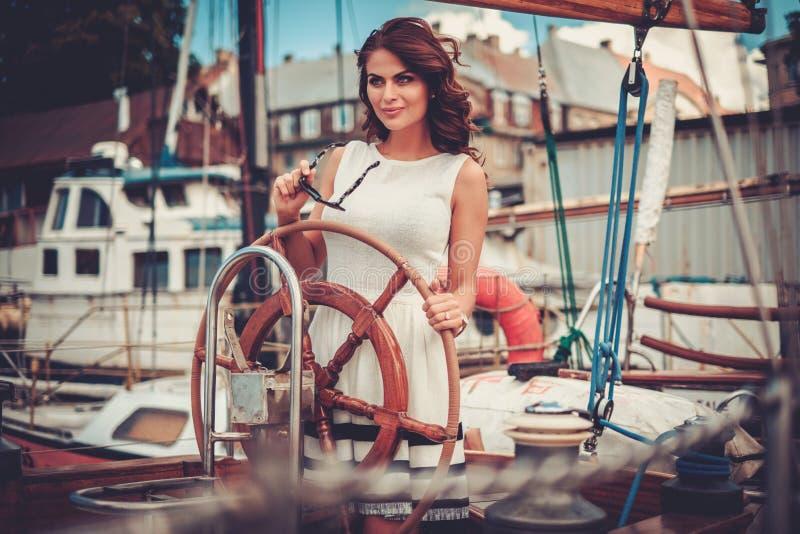 Stilfull förmögen kvinna på en lyxig träregatta royaltyfri foto