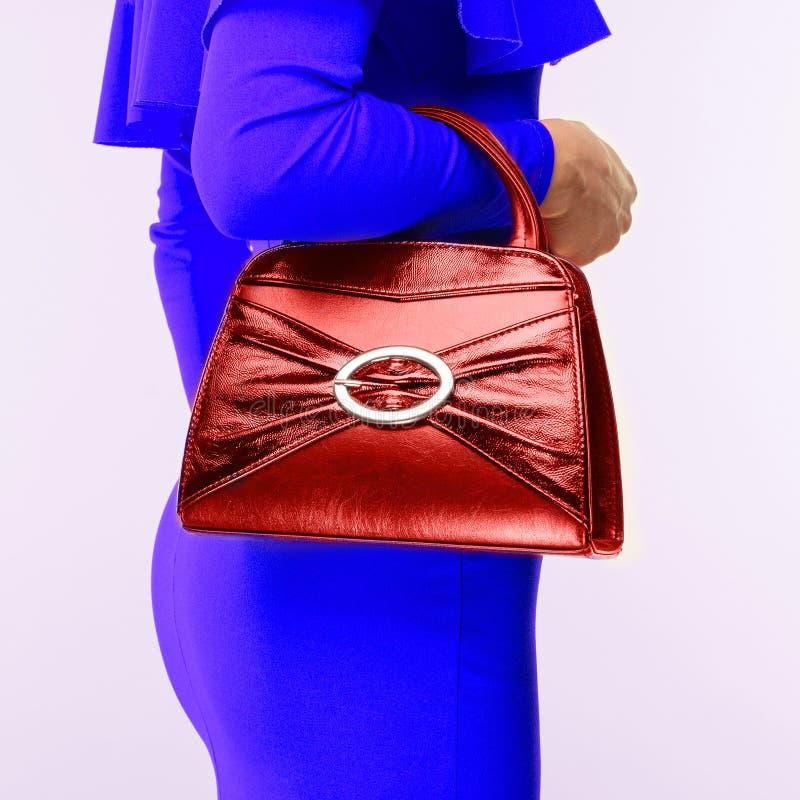 Stilfull flicka i blå klänning med den röda handväskan arkivfoton
