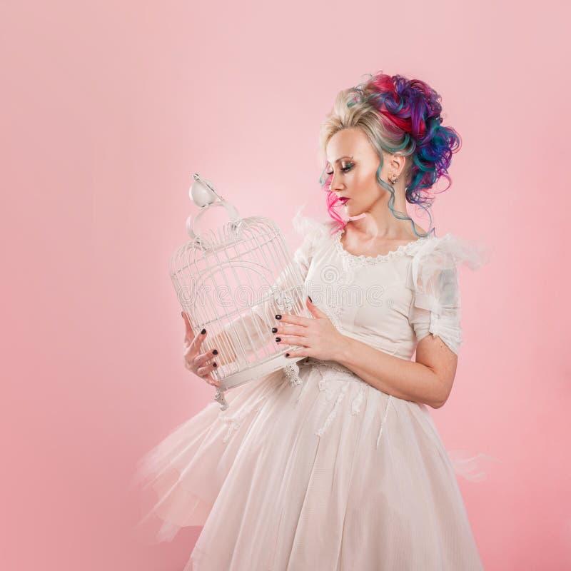 Stilfull flicka i den vita klänningen Idérik hårfärgläggning Mång--färgad frisyr Begrepp med en tom fågelbur royaltyfri fotografi
