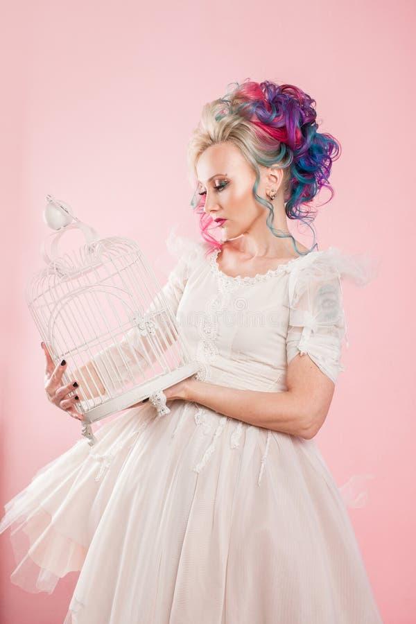 Stilfull flicka i den vita klänningen Idérik hårfärgläggning Mång--färgad frisyr Begrepp med en tom fågelbur arkivbild