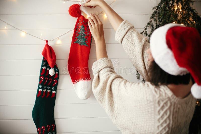 Stilfull flicka i hemtrevlig tröja och den santa hatten som dekorerar rum för julferier med strumpor, girlandljus och julträdet royaltyfri fotografi