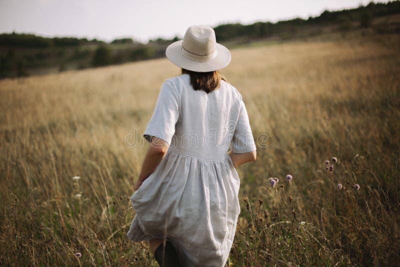 Stilfull flicka i linneklänning som går bland örter och vildblommor i solig äng i berg Boho kvinna som kopplar av i bygd, royaltyfri foto