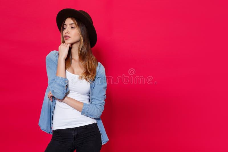 Stilfull flicka i tillfällig kläder och bruna hatten som poserar med attitudine i studio över ljusröd bakgrund royaltyfri foto
