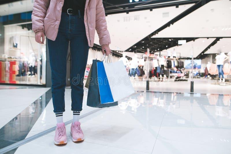 Stilfull flicka med shoppingpåsar i hennes hand mot bakgrunden av ett bekläda lager i gallerian ben för bakgrundspåsebegrepp som  royaltyfri foto