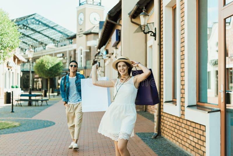 Stilfull flicka med shoppingpåsar som går på gatan, hennes pojkvän som bakom går arkivfoton