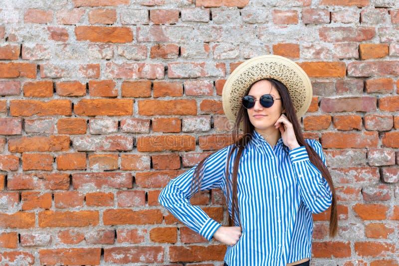 Stilfull flicka som framme poserar av tegelstenväggen arkivbild