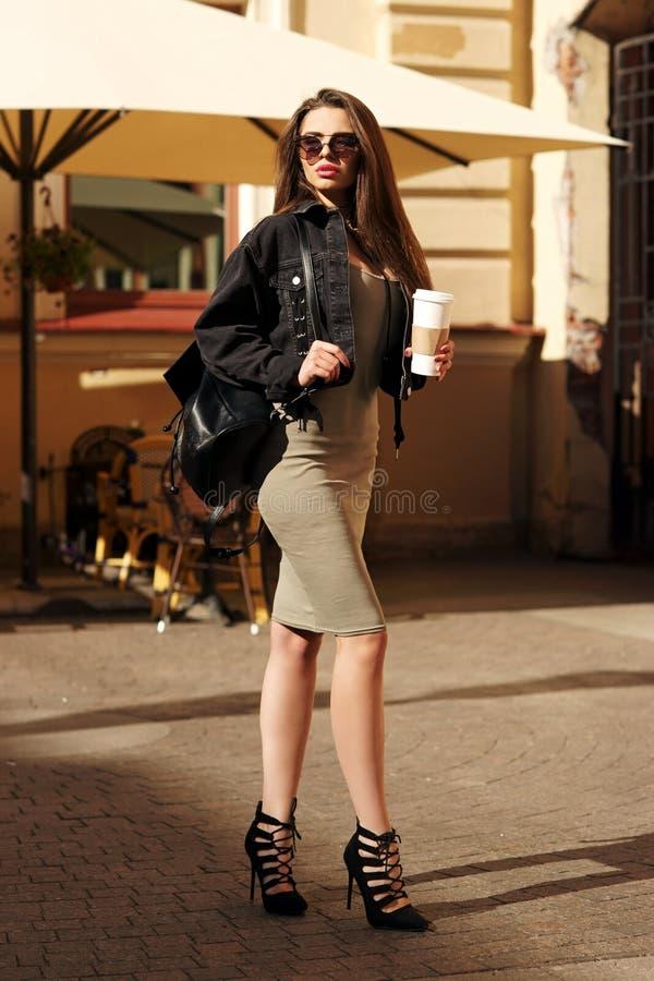 Stilfull flicka som går i stad royaltyfri foto