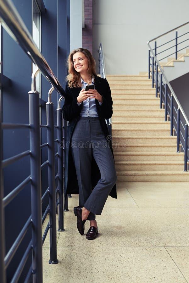 Stilfull flicka som smsar via celltelefonen arkivbilder