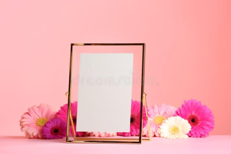 Stilfull fotoram och härliga blommor på tabellen mot färgbakgrund arkivfoto