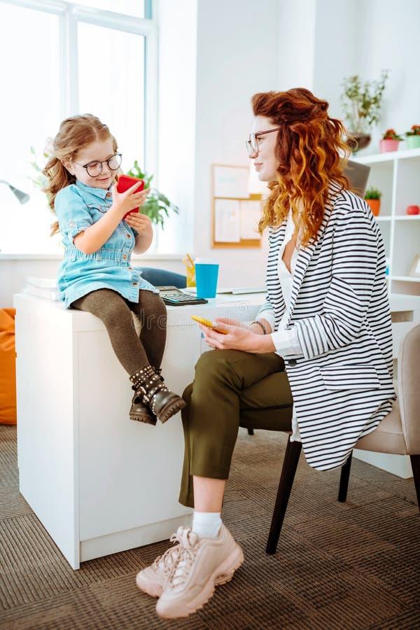 Stilfull freelancer som ser hennes roliga dotter som använder smartphonen arkivfoton