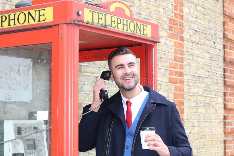 Stilfull gentleman som kallar från tappningpayphonen arkivfoton