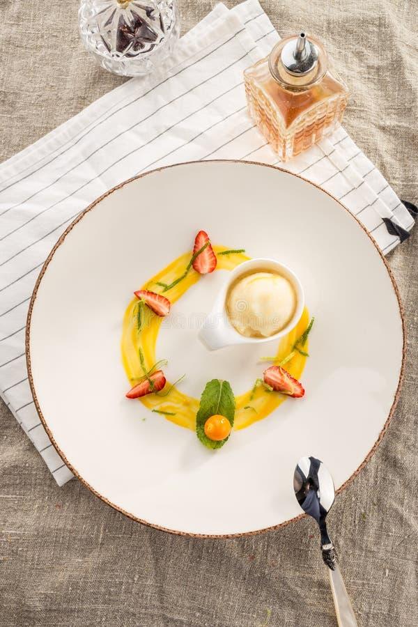 Stilfull gourmet- efterrätt med vaniljglass och frukt som tjänas som på den vita plattan på restaurangen arkivbild