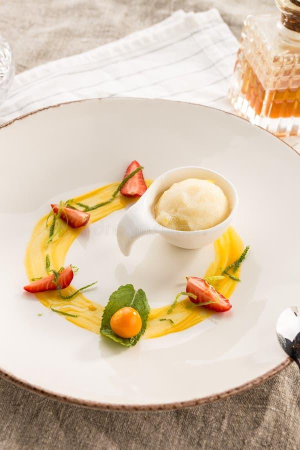 Stilfull gourmet- efterrätt med vaniljglass och frukt som tjänas som på den vita plattan på restaurangen fotografering för bildbyråer