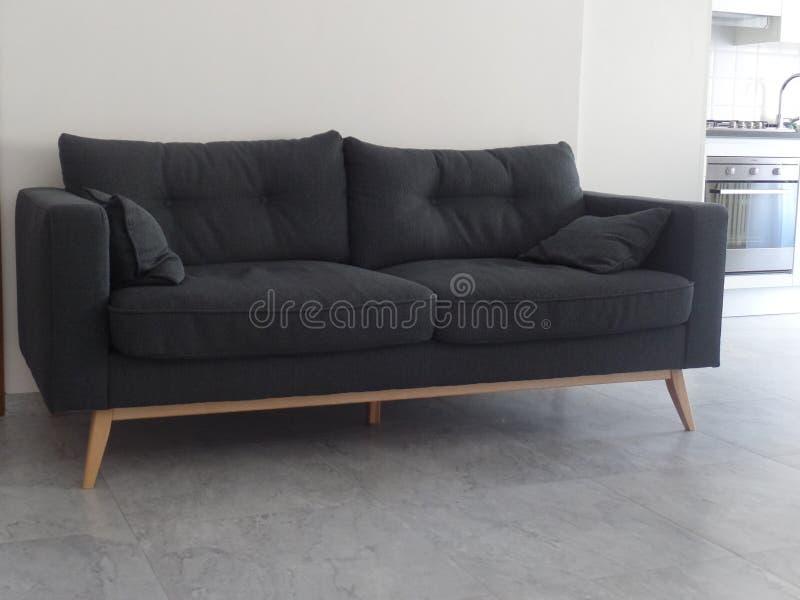 Stilfull grå soffa i en öppen planvardagsrum royaltyfri foto