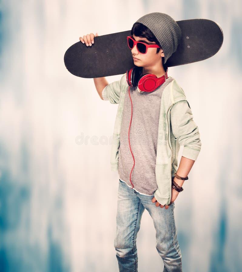 Stilfull grabb med skateboarden arkivfoto