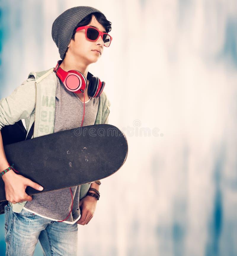 Stilfull grabb med skateboarden royaltyfria foton