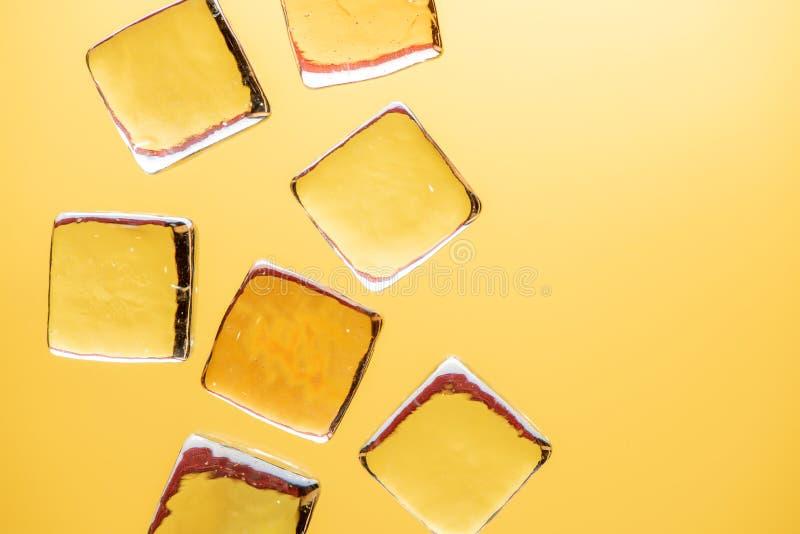 Stilfull gul bakgrund med genomskinligt is-som kuber för drinkar Plant lekmanna- makrofoto royaltyfri foto