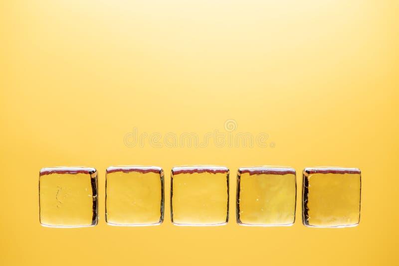 Stilfull gul bakgrund med genomskinligt is-som kuber för drinkar Plant lekmanna- makrofoto arkivbild