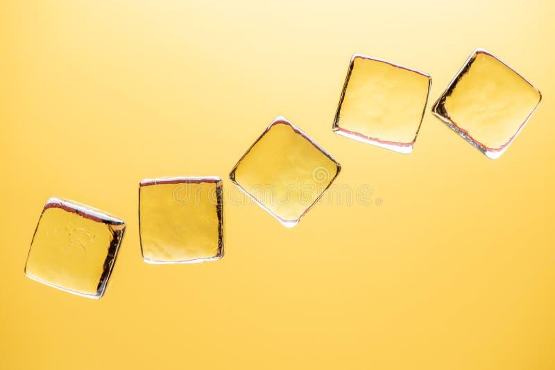 Stilfull gul bakgrund med genomskinligt is-som kuber för drinkar Plant lekmanna- makrofoto arkivfoto