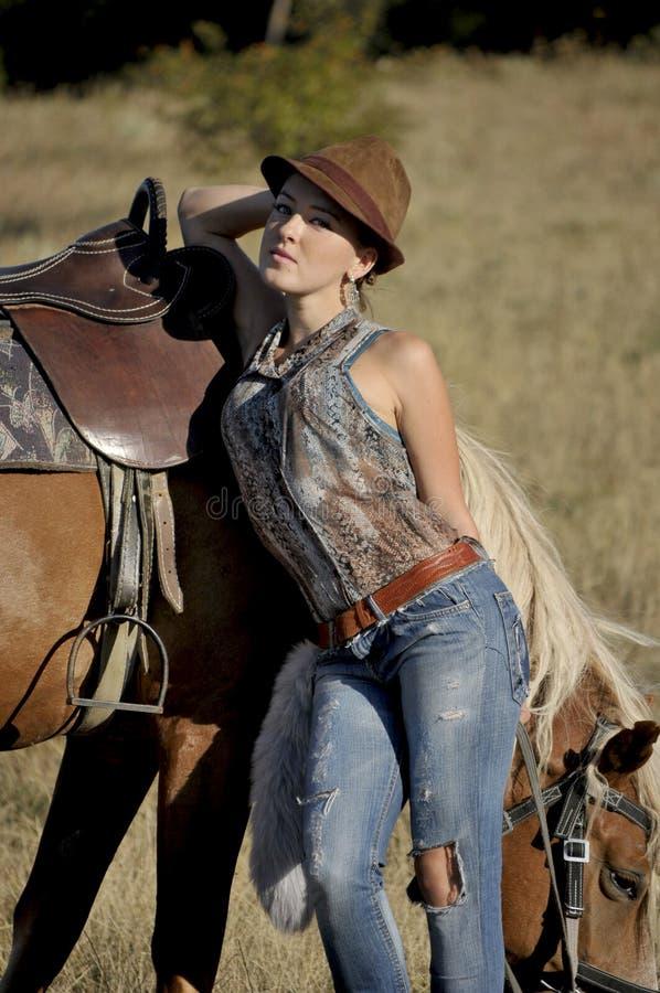 Stilfull gullig flicka som poserar nära häst i moment arkivbild