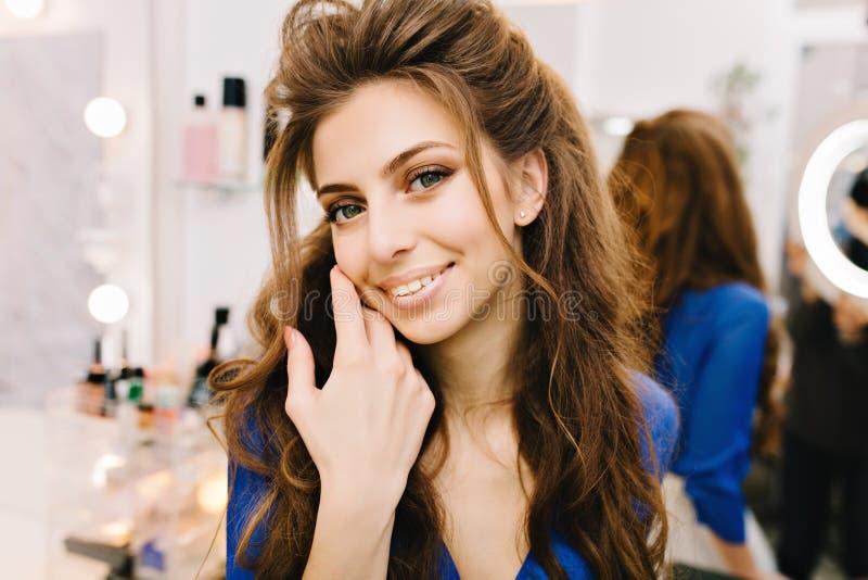 Stilfull gullig ung kvinna för Closeupstående med långt brunetthår som ler till kameran i frisörsalong _ royaltyfri foto