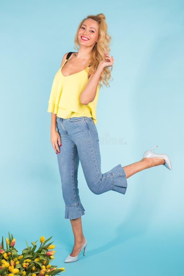 Stilfull härlig blond ung kvinna som poserar på blå bakgrund fotografering för bildbyråer