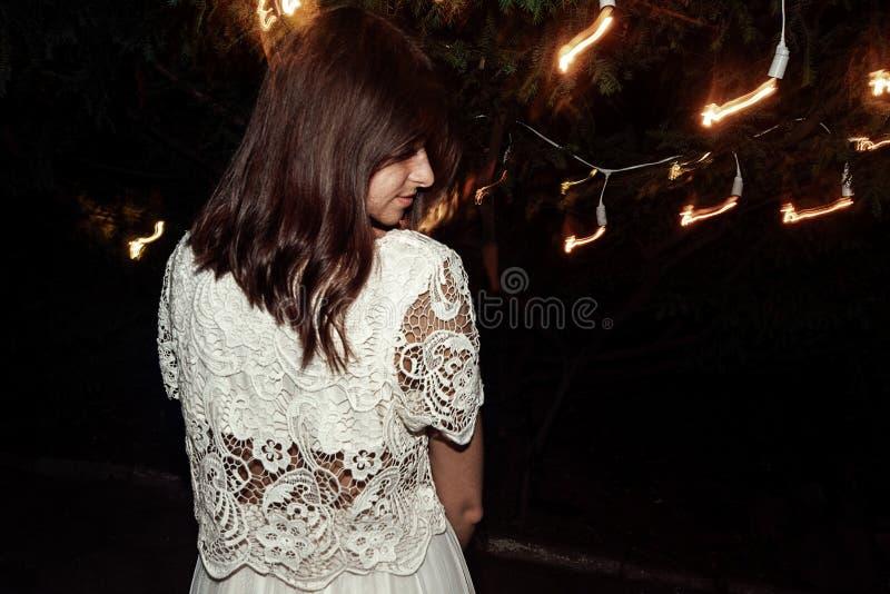 Stilfull härlig brunettflicka i tappningdrees i aftonen royaltyfri foto