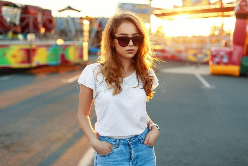 Stilfull härlig flicka i solglasögon på solnedgångbakgrund arkivbilder