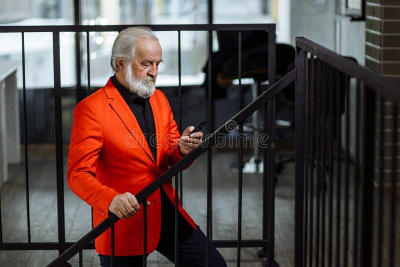 Stilfull hög affärsman som använder smartphonen, medan klättra trappan royaltyfria foton
