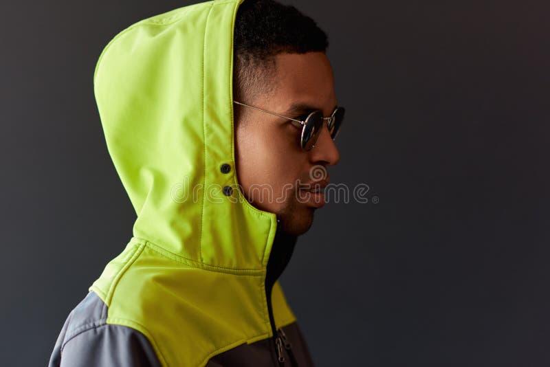 Stilfull hipsterafrikansk amerikanman som ser till och med spegelsolglasögon, hoody bärande grön sport och att posera på den svar royaltyfri bild