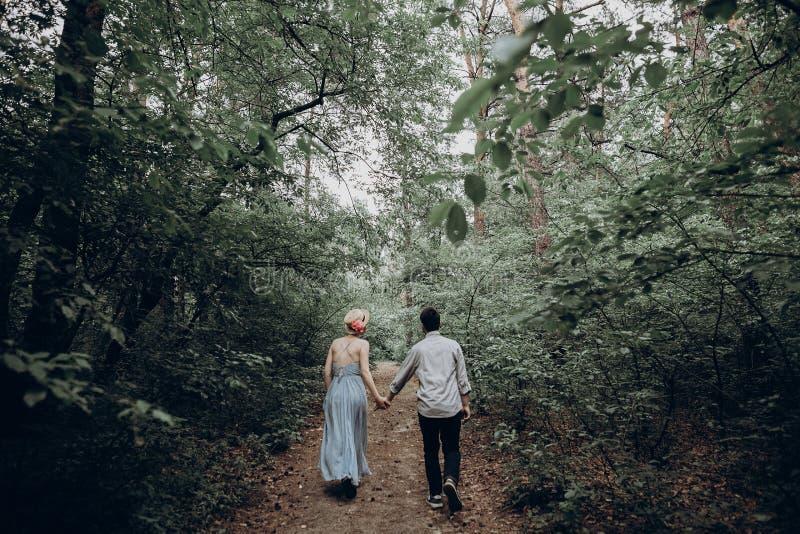 Stilfull hipsterbrud och brudgum som går i grön sommarskog royaltyfri bild